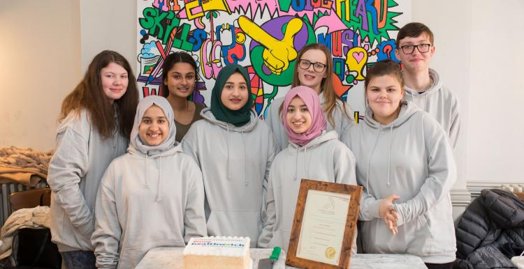 Group of young volunteers with certificate and cake
