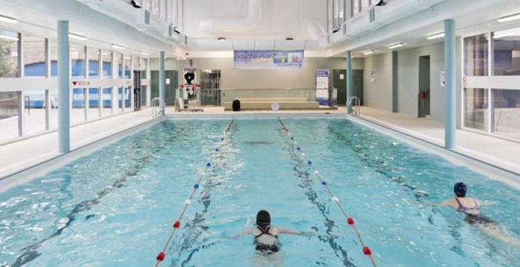 Two people swimming in an indoor pool at Golden Lane