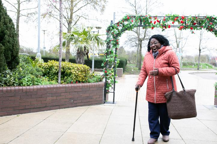 Happy smiling woman after she has walked through an Arch of Roses in the park
