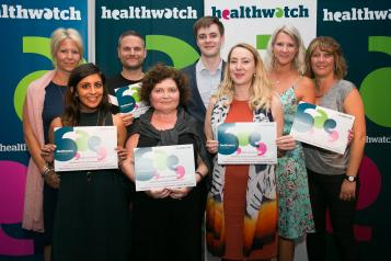 Group of people with certificates at healthwatch event