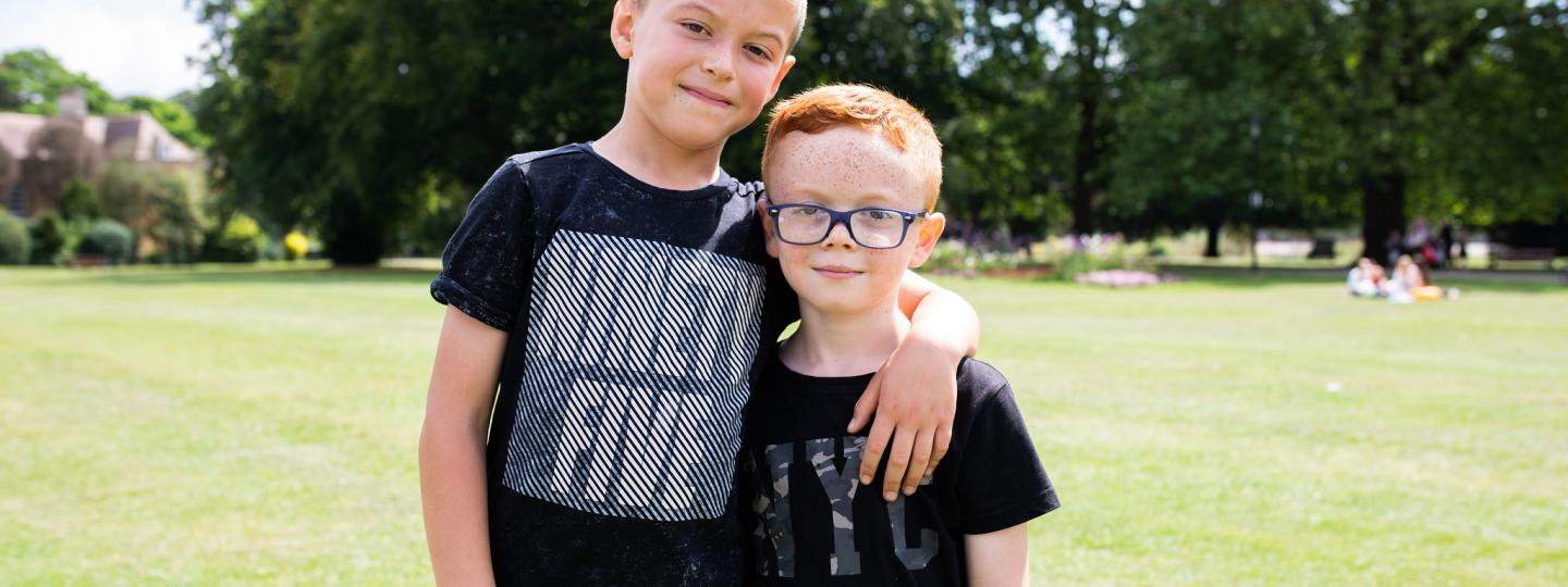Older brother with his arm around his younger brother in the park