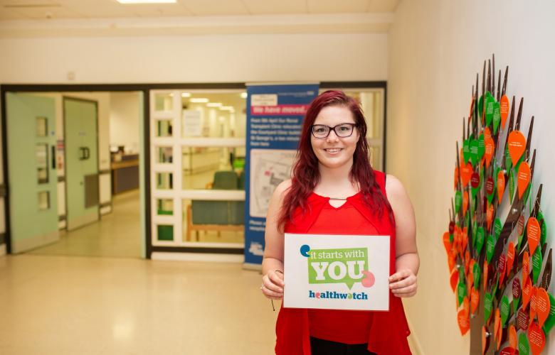 woman holding it starts with you campaign poster in foyer